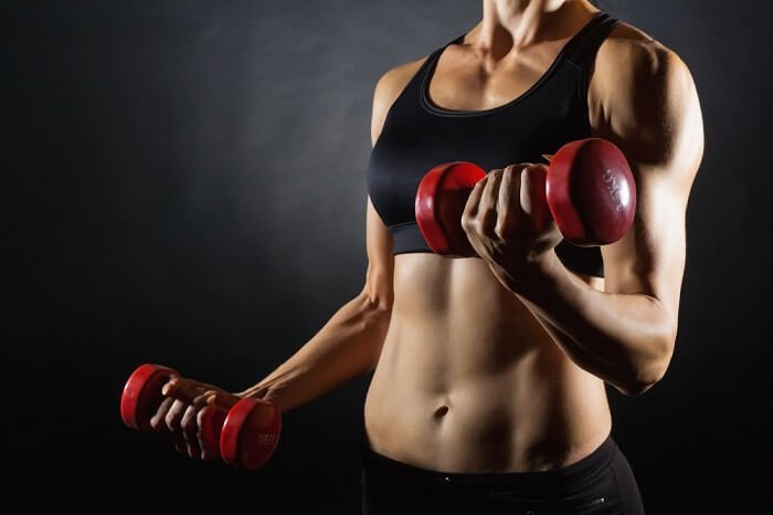 fit woman holding red dumbbells doing sets and reps