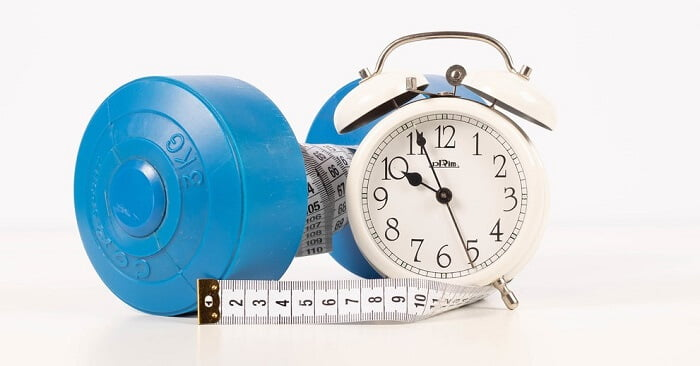 blue dumbbell, measuring tape and an alarm clock on a white surface