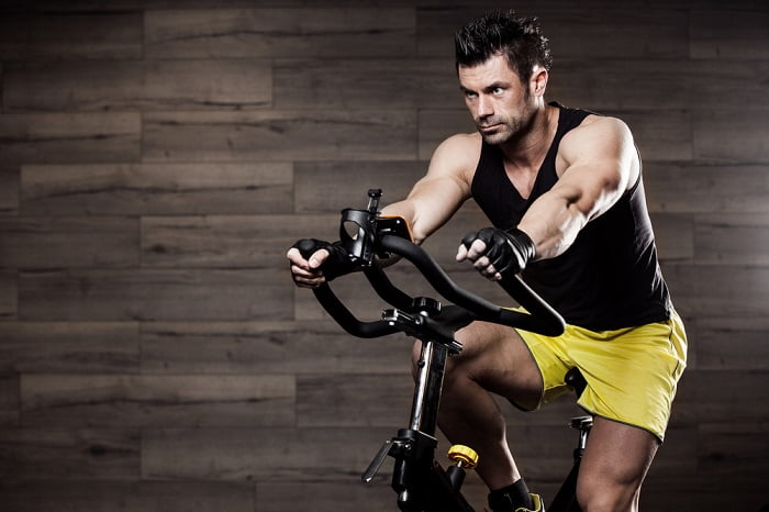 man in a yellow shorts wokring out on a cardio machine
