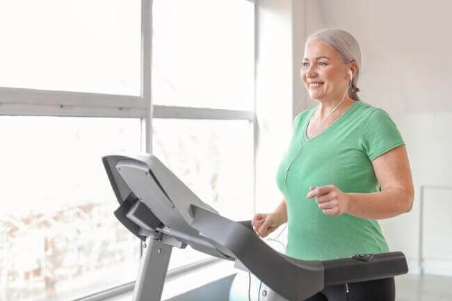 senior woman exercising on her treadmill at home