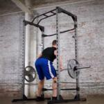 man perfroming bent over barbell rows inside fitness reality 810XLT power cage
