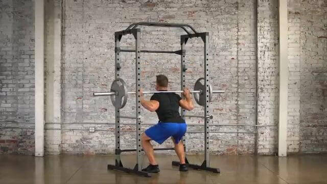 man performing squats inside progear 1600 ultra strength rack
