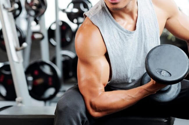 strong man doing seated dumbbell curl