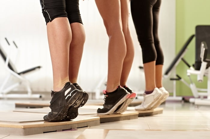 three women standing tiptoe in a gym doing exercises for calves