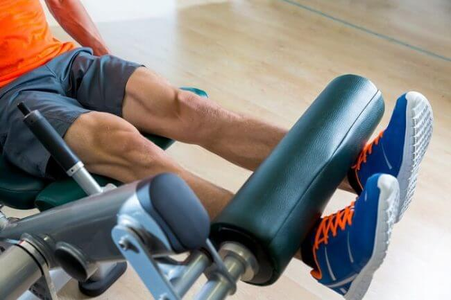 fit man doing leg extension exercise on a machine