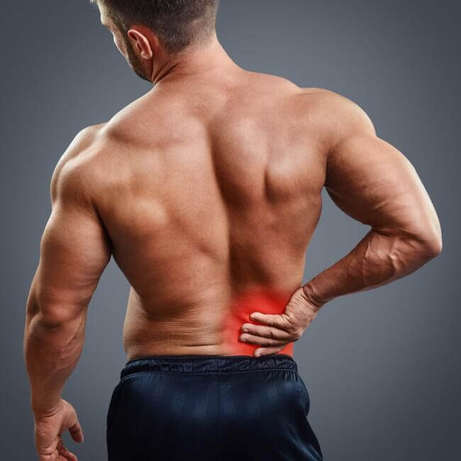 bodybuilder holding his hand on lower back that is in pain