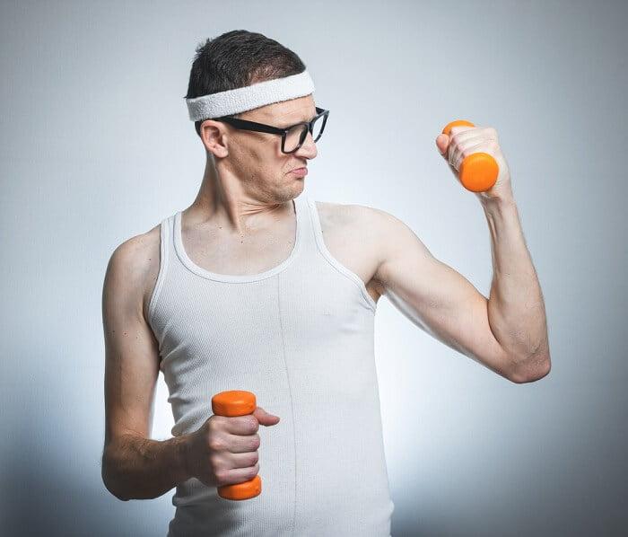 very weak and skinny man lifting small orange dumbbells