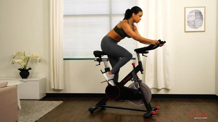 woman cycling on spin bike at home
