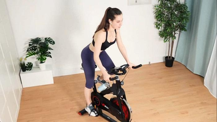 woman standing and cycling on vigbody exercise bike