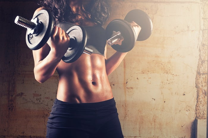 young fit woman holding dumbbells