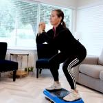 woman performing squats on vibration plate in her home