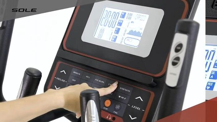 woman selecting resistance levels SOLE E25 Elliptical monitor