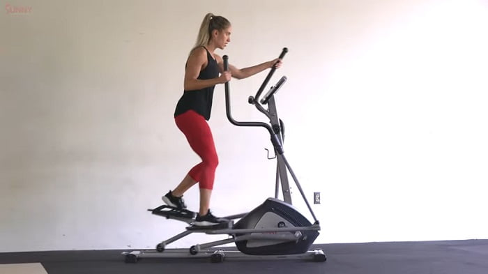 woman exercising on elliptical in home gym