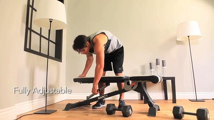 man adjusting marcy weight bench to flat position