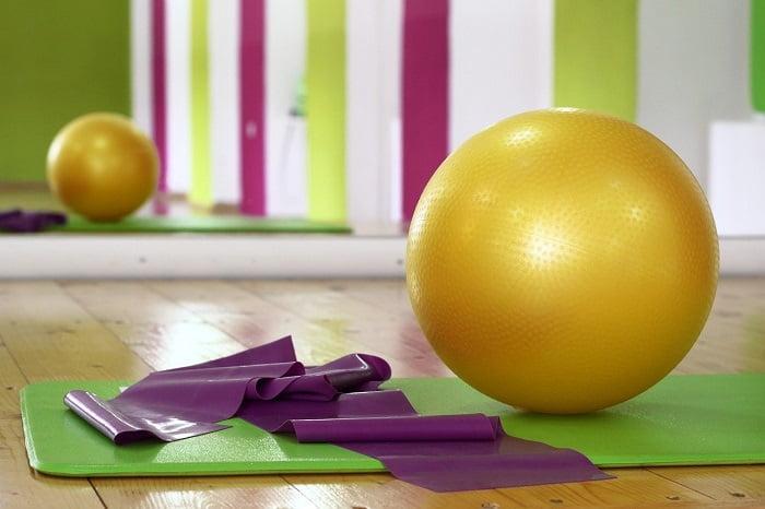 yellow Pilates ball on a green mat