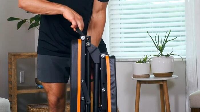 man folding gymenist weight bench