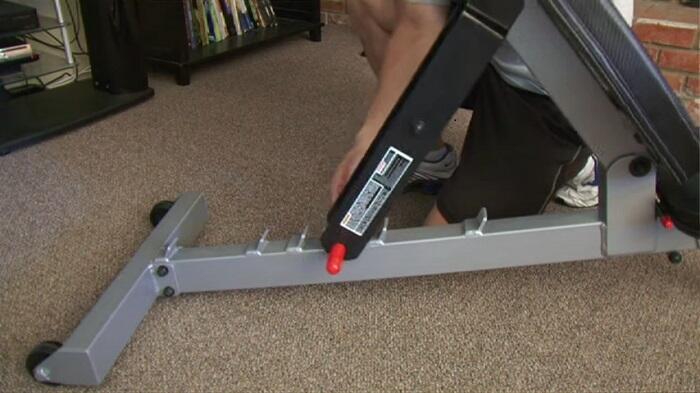 man adjusting powerblock sports bench back pad
