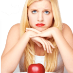 young woman sitting in front of a plate with an apple and a fork