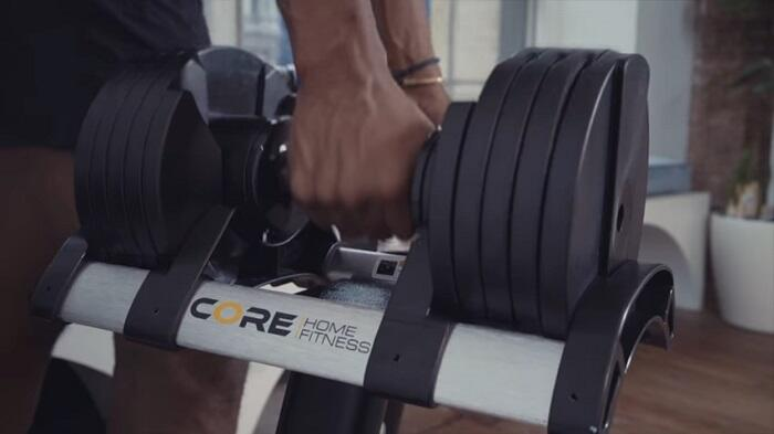 man holding two dumbbells core fitness