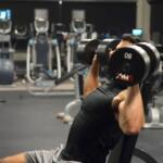 man dumbbell pressing in commercial gym