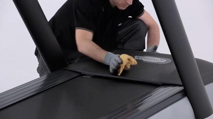 man dusting his treadmill