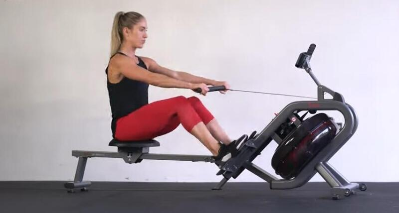 attractive woman rowing on a water rower