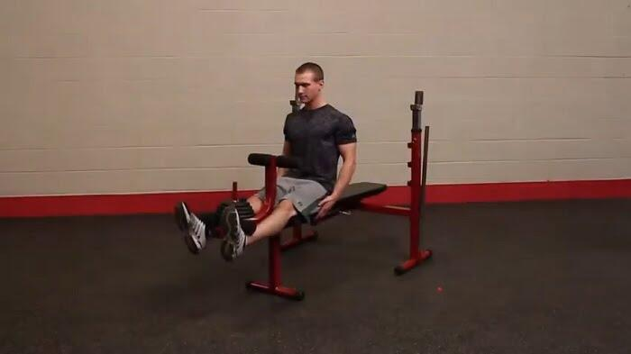man performing legs curls ob best fitness olympic bench