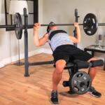 man performing bench on competitor olympic weight bench
