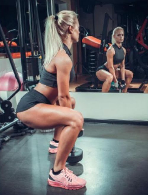 fit young woman doing squats with a dumbell