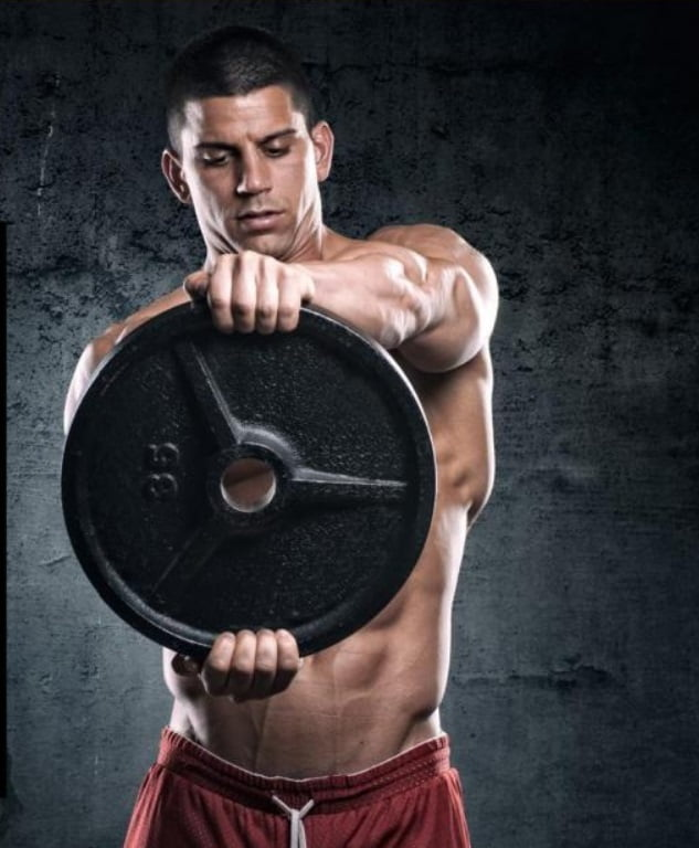 fit man holding a weight plate in front of him
